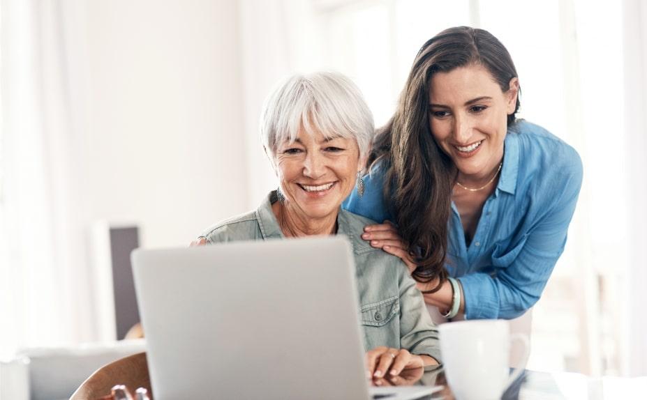 Two women smiling using a laptop.