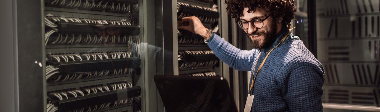 Business Man adjusting server rack while holding laptop