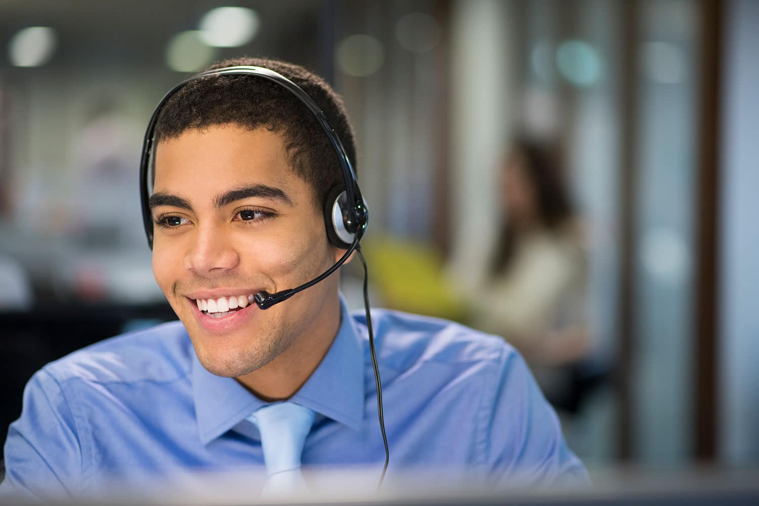 Smiling man using ToldeoTel VoIP system.